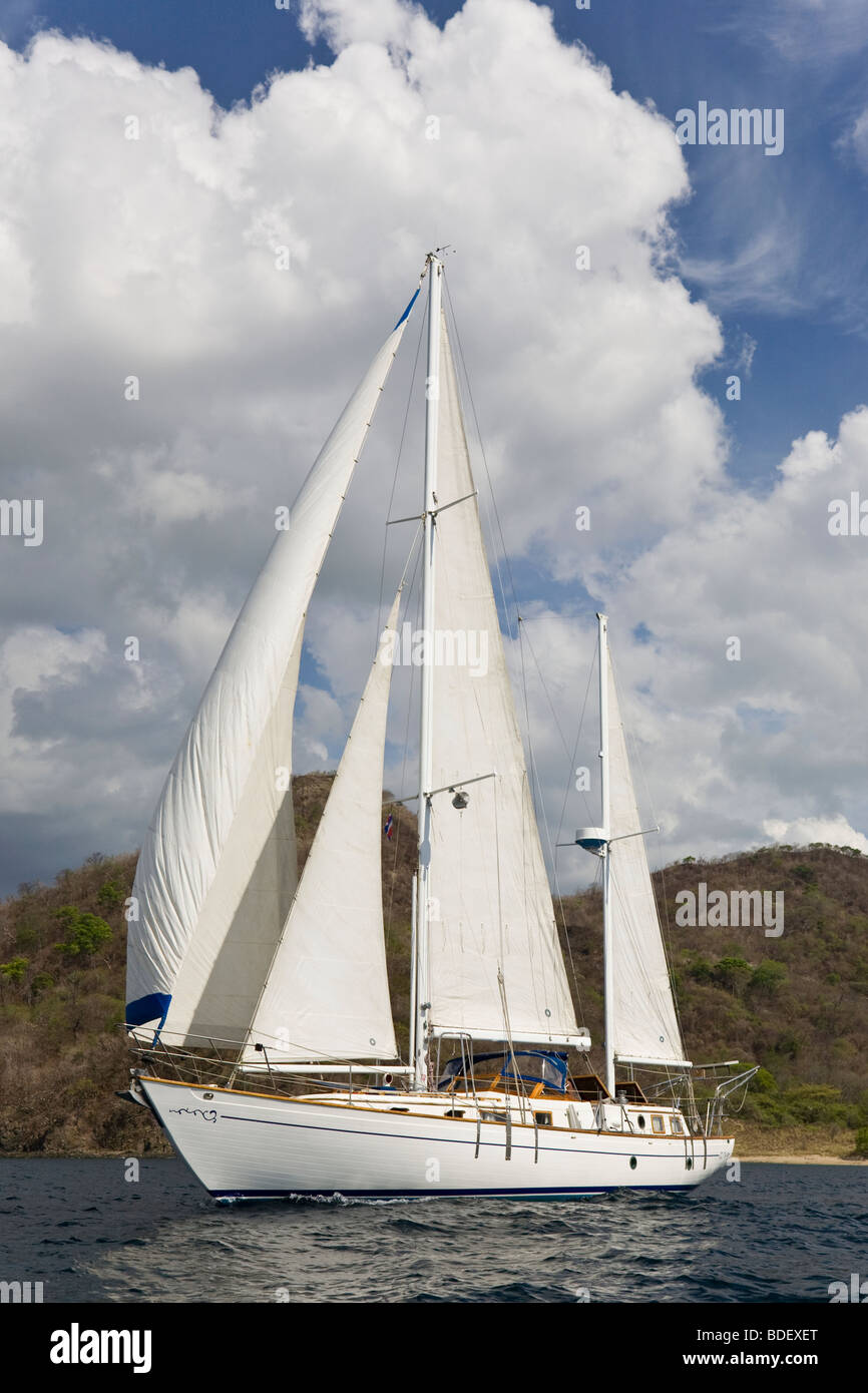 Ketch rig sailboat cruising along the shoreline in the Papagayo Bay, Guanacaste, Costa Rica. - Stock Image