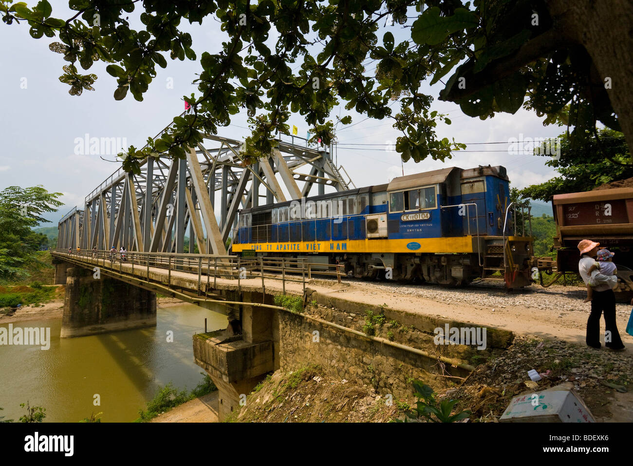 A blue and yellow goods train pulling minerals crosses a steel bridge across a river in the highlands of Vietnam Stock Photo