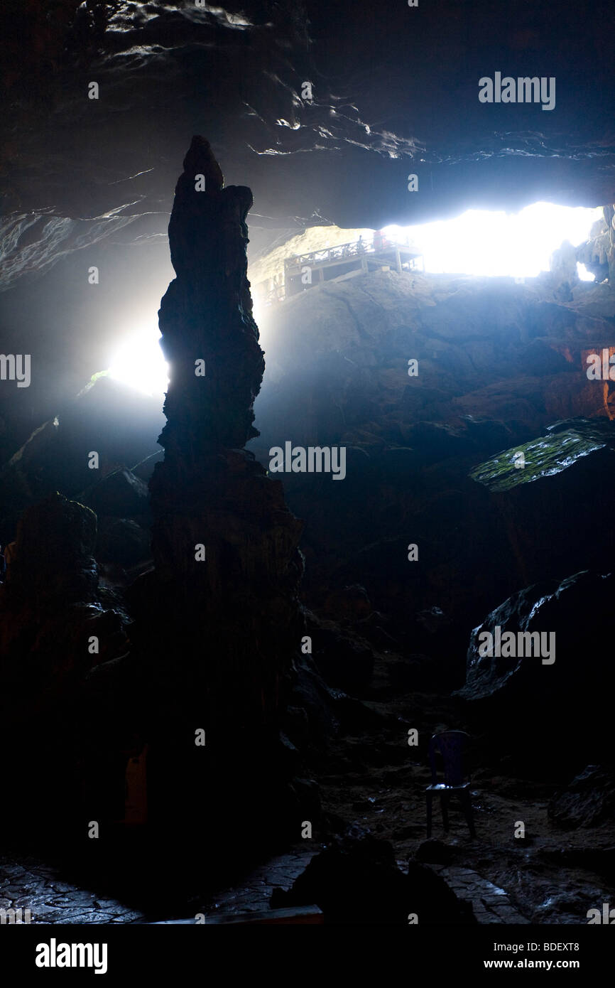 A huge stalagmite before the halo of light at the cave entrace of Hai Phong cave, Ha Long Bay, Vietnam - Stock Image