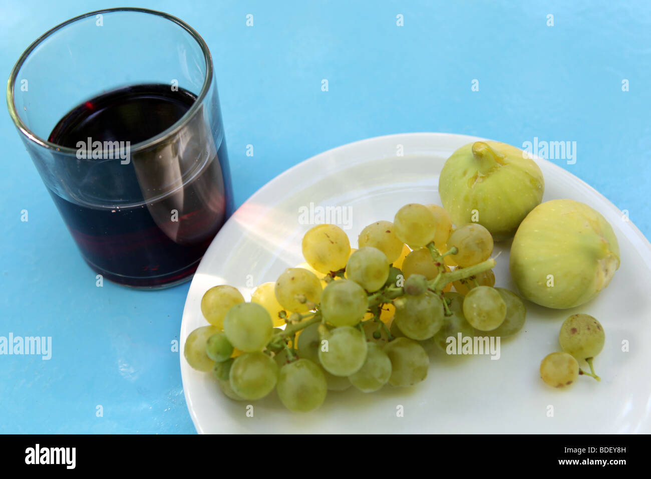 A Greek snack of red wine with a plate of grapes and figs on a blue table. - Stock Image