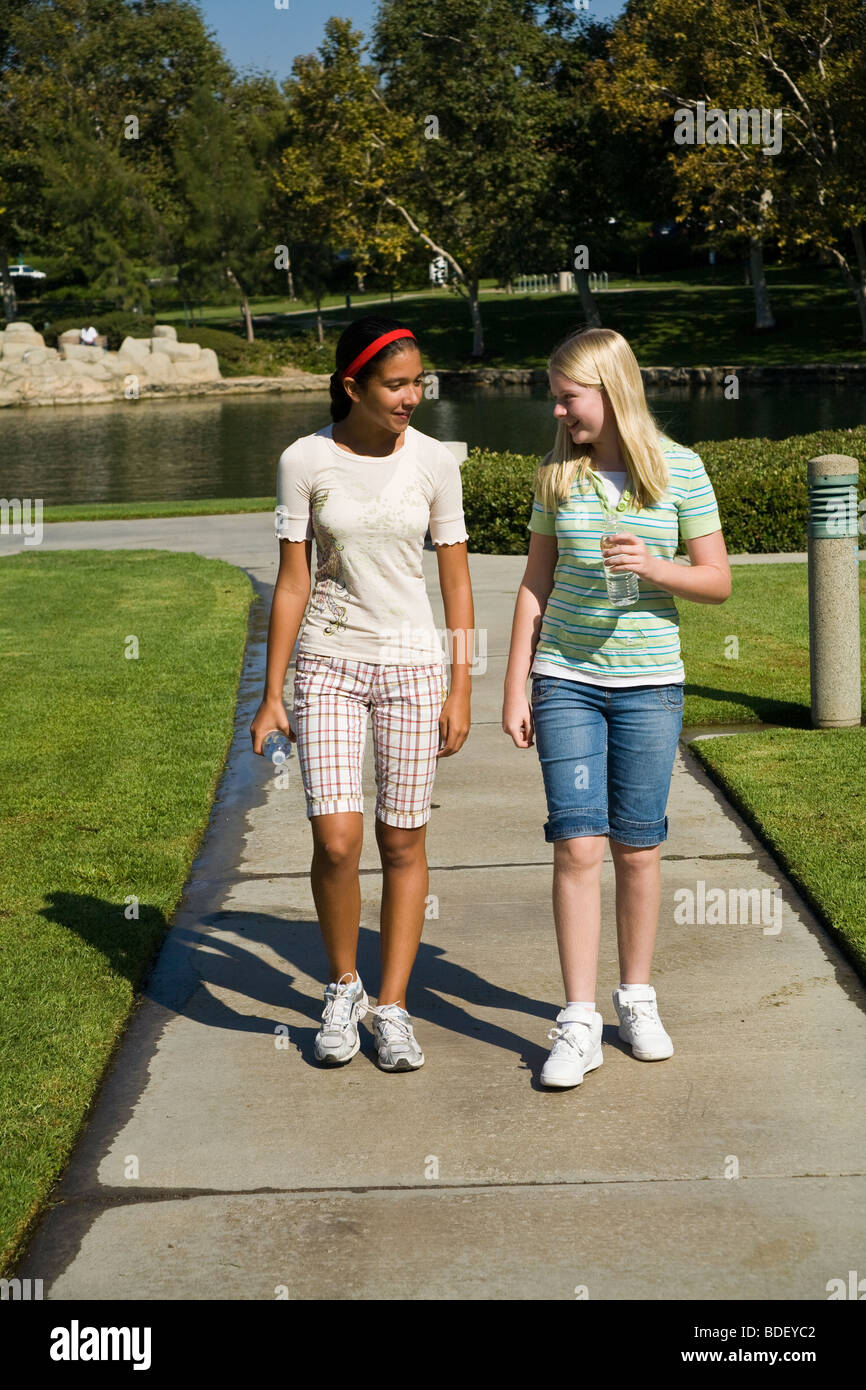 Hispanic & Caucasian junior high child children young person people  Tween tweens girl girls walk walking talking Stock Photo