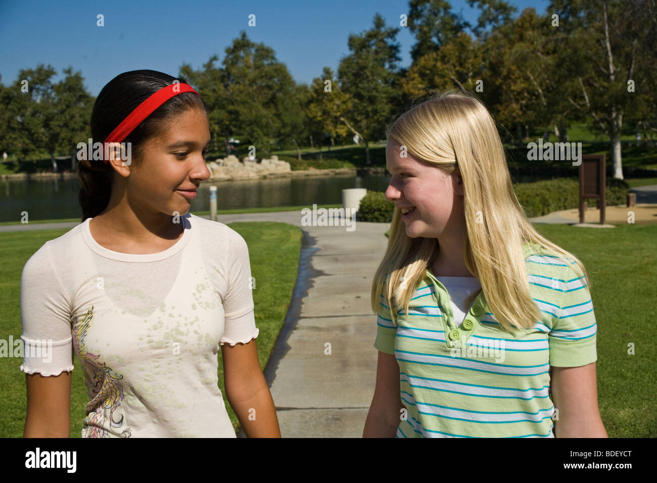 Two girls hang hanging out together.Hispanic and Caucasian junior high girls walking in the park. MR - Stock Image