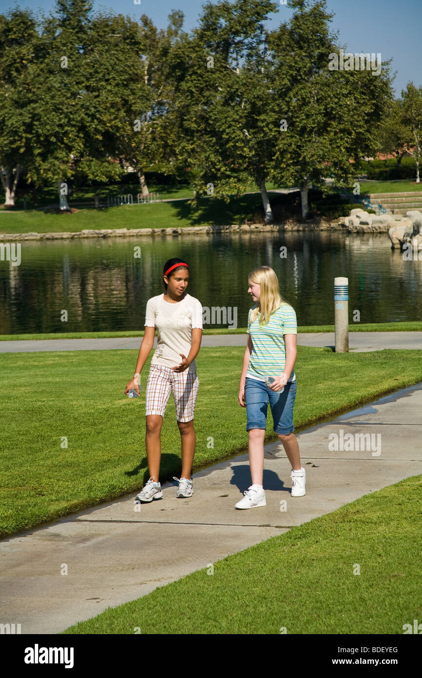 Two racial mixed racially mixed girls hang hanging out together.Hispanic and Caucasian junior high girls walk Walking - Stock Image