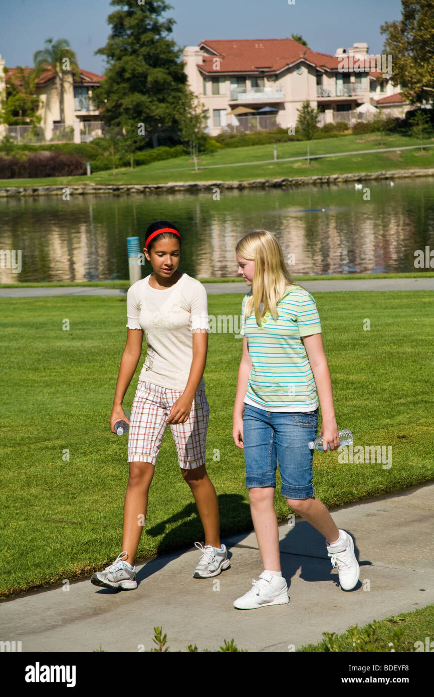 Tween tweens  hanging out Hispanic and Caucasian teenage girls walking and talking in the park. MR ©Myrleen - Stock Image