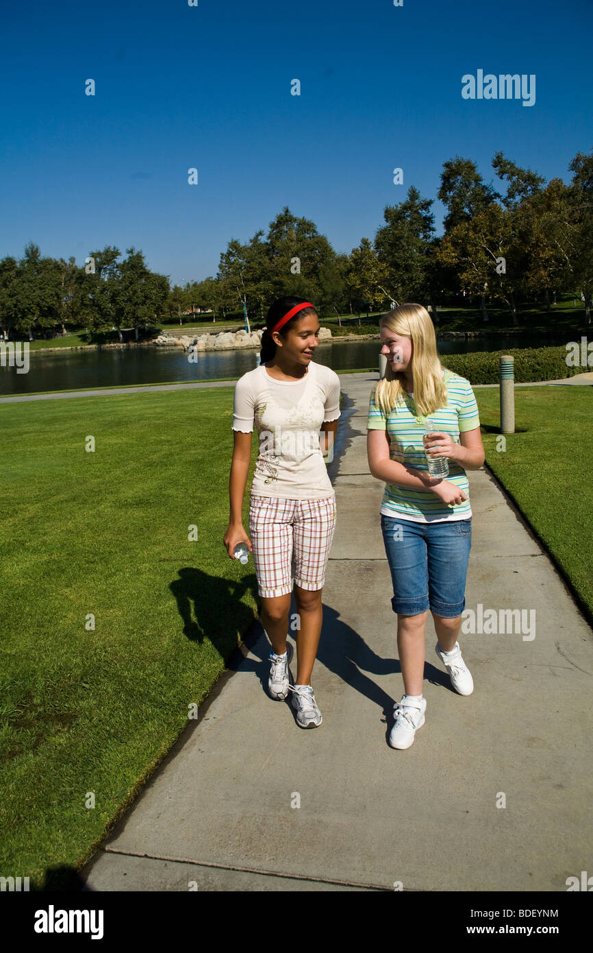 Hispanic and Caucasian hanging out  two racial mix racially mixed  girls walking in the park. MR - Stock Image