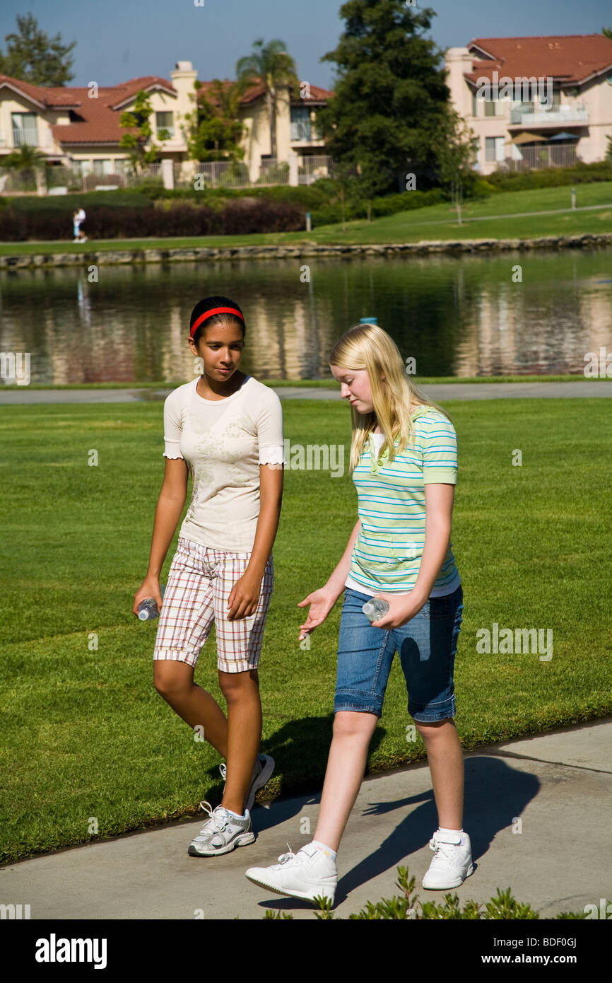 Hispanic and Caucasian junior high girls walking in the park. MR - Stock Image