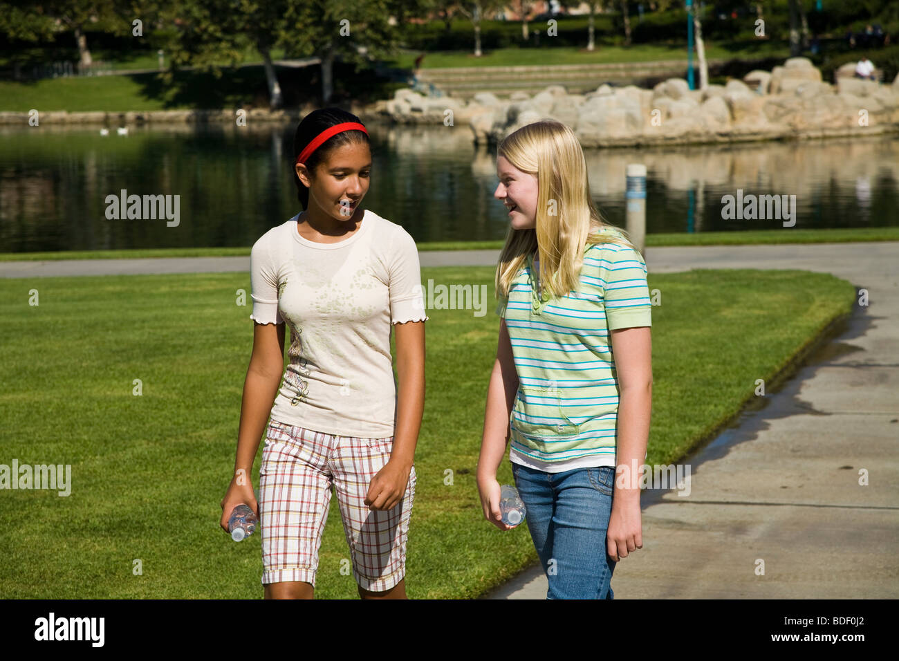 Two girls 11-13 year old hang hanging out together Hispanic and Caucasian girls walk Walking sidewalk Tween tweens - Stock Image