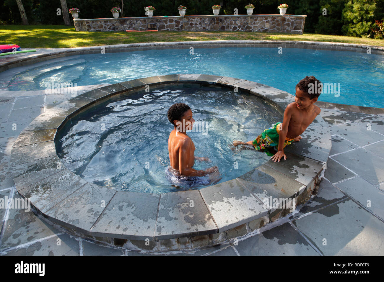 Two boys, eight and ten years old, play in a backyard swimming pool, Sag Harbor, New York - Stock Image
