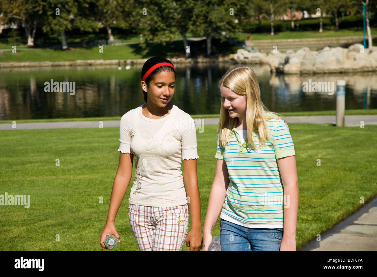 Two girls hang hanging out together. Hispanic and Caucasian junior high girls walking in the park. MR - Stock Image