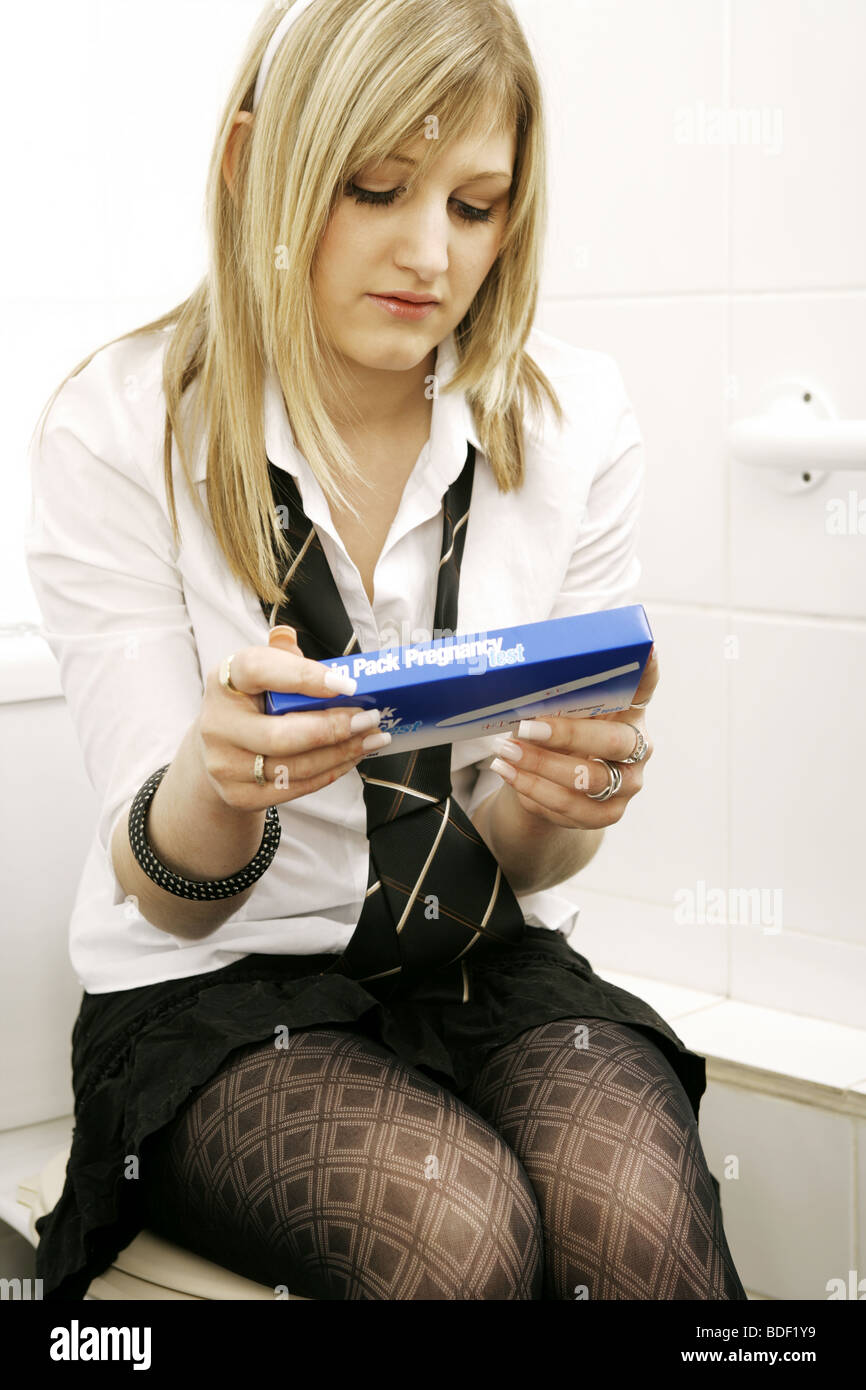 Young Teenage girl wearing school uniform,sitting on a toilet seat holding a pregnancy tester in her hand. - Stock Image