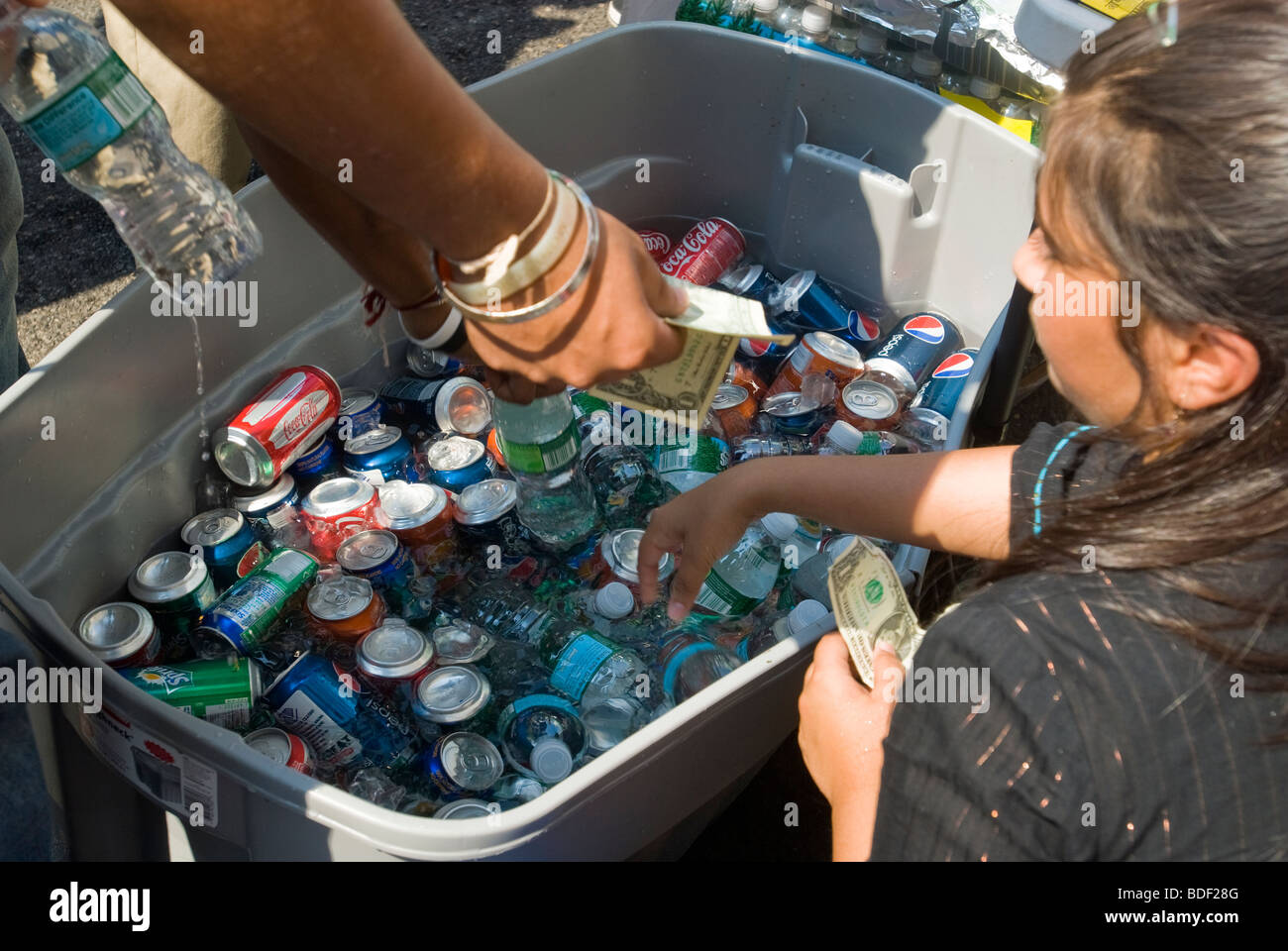 Cans of ice cold soda and water in a container of ice are sold by an entrepreneur at a street fair in New York Stock Photo
