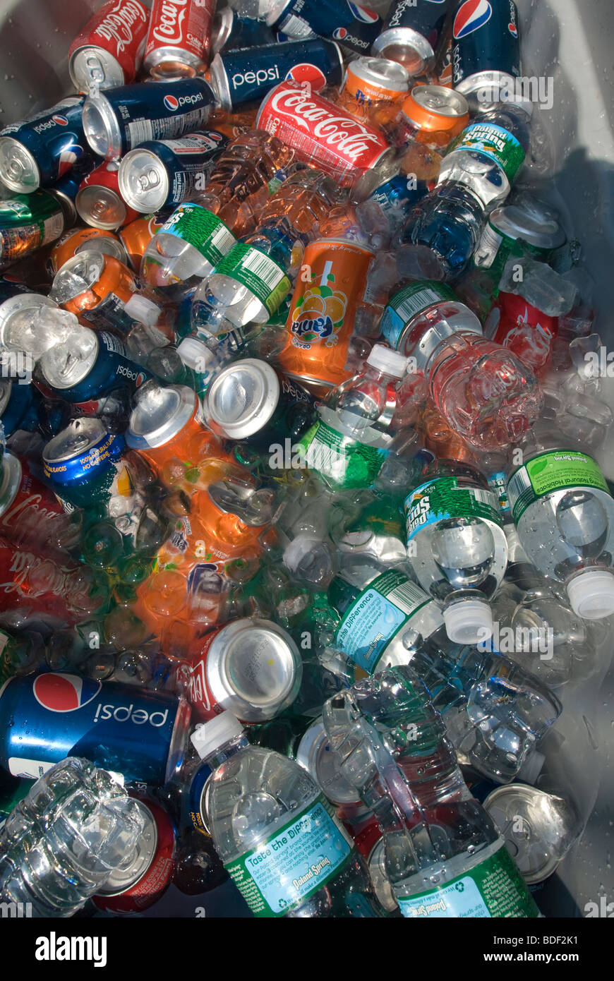 Cans of ice cold soda and water in a container of ice are sold by an entrepreneur at a street fair in New York - Stock Image