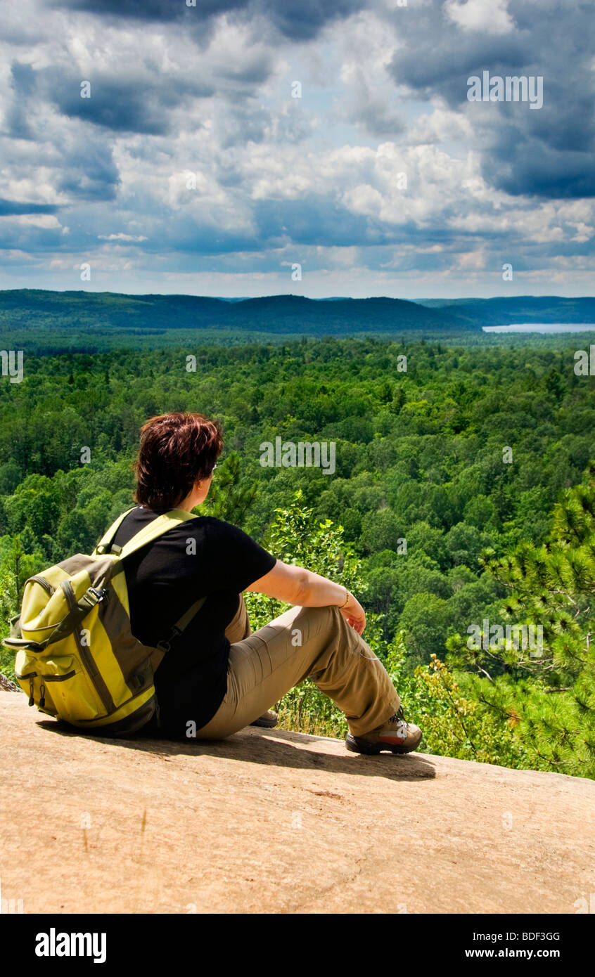 A female hiker looking out over Algonquin Provincial Park in Ontario, Canada, from a high viewpoint on the Lookout - Stock Image