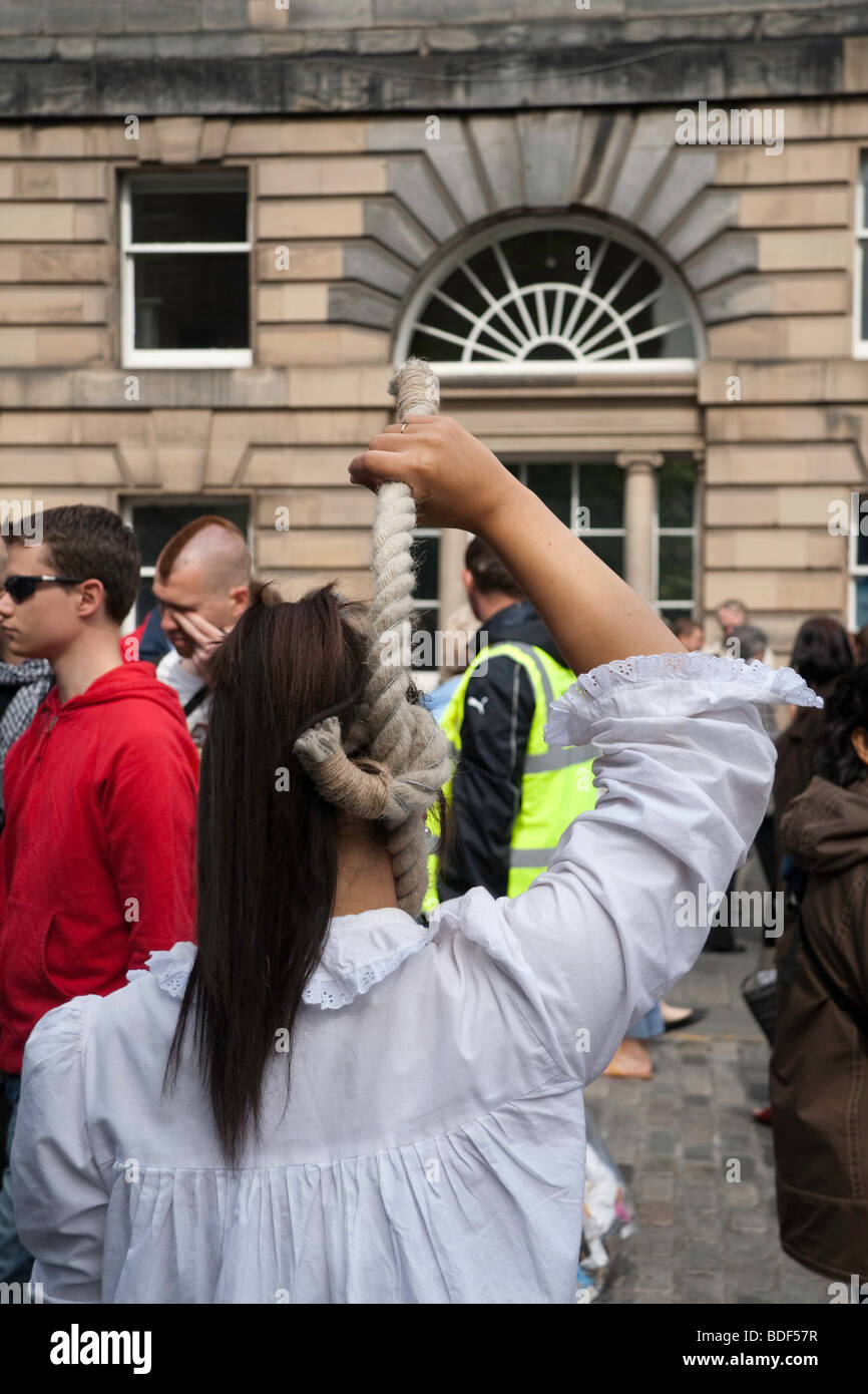 A street performer holds a rope noose around her neck on Edinburgh's Royal Mile as part of the Fringe Festival - Stock Image