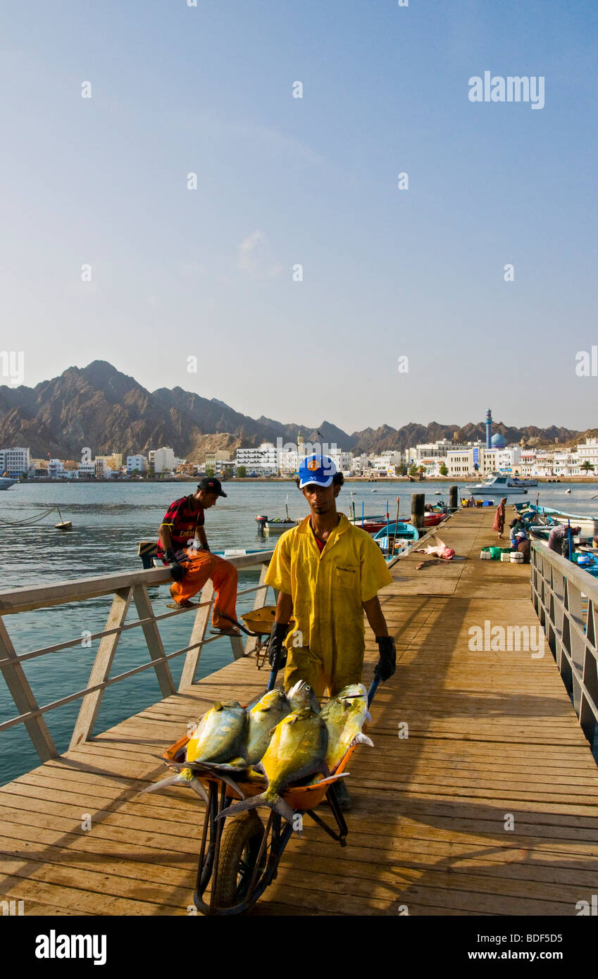 Fishermen at The Mutrah Fish docks with Old Muscat in the Background - Stock Image