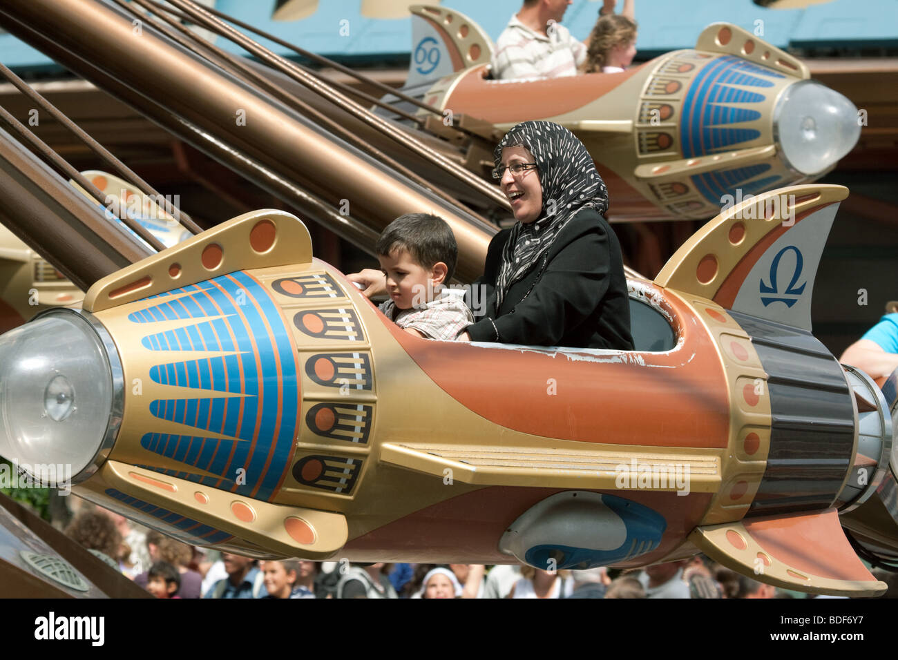 A family enjoys a ride on a rocket roundabout, disneyland paris France - Stock Image