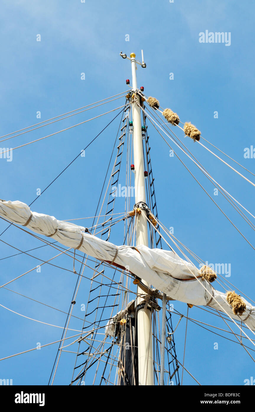 Upper mast with sail furled on yardarm, shrouds, rigging, lines and halyards - Stock Image