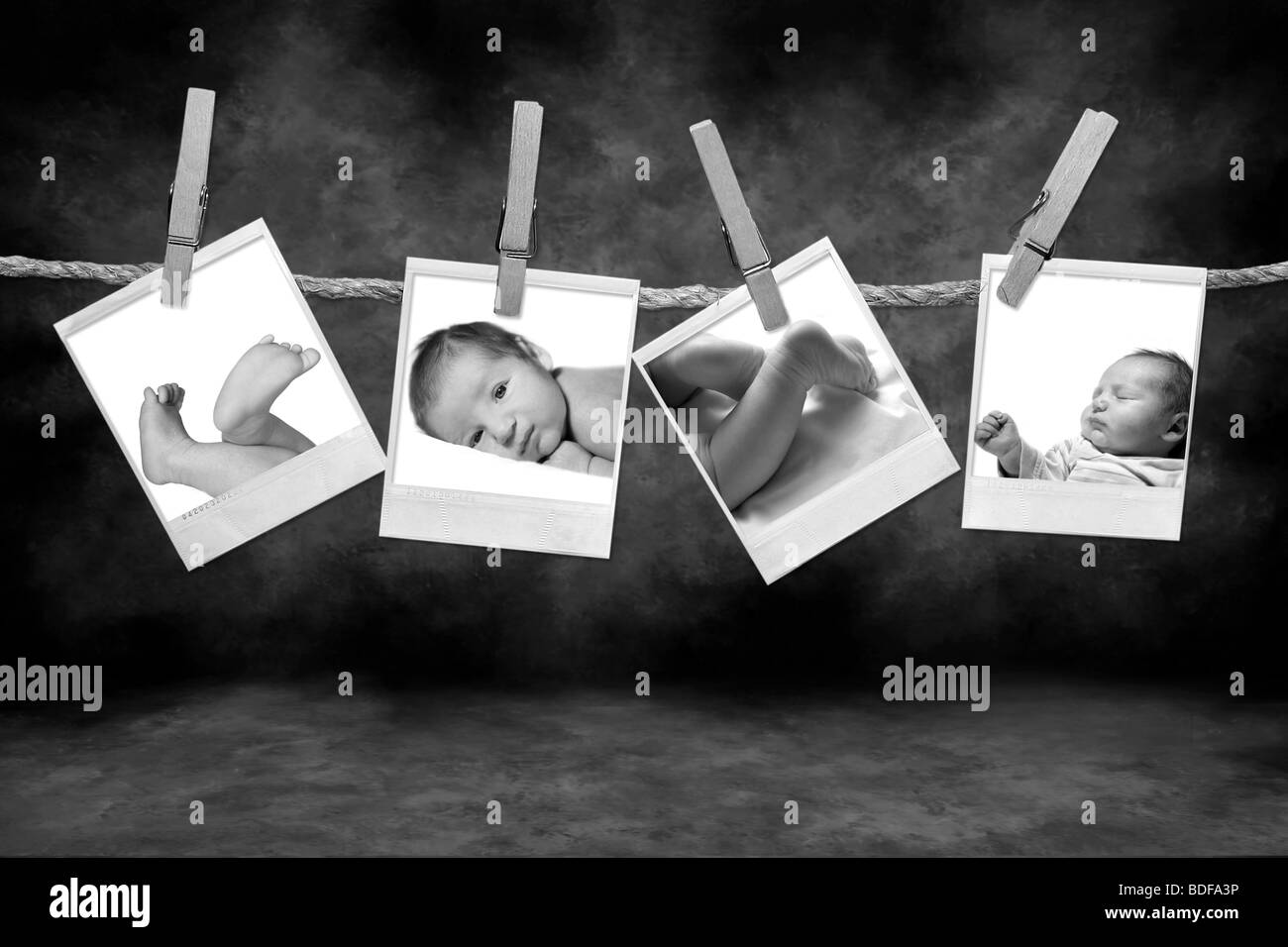 Black and White Photographs Hanging on a Rope By Clothespins on a Grunge Background - Stock Image