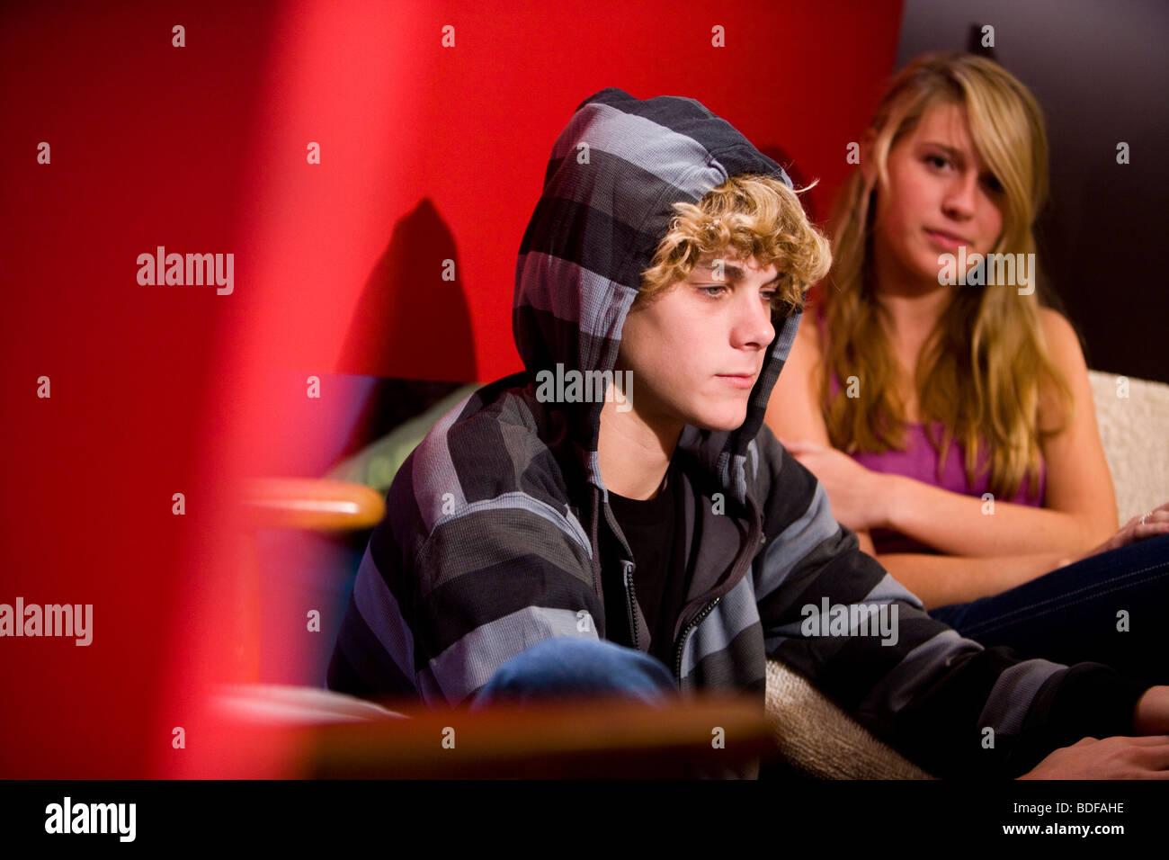 Young unhappy teenage couple sitting on sofa indoors - Stock Image
