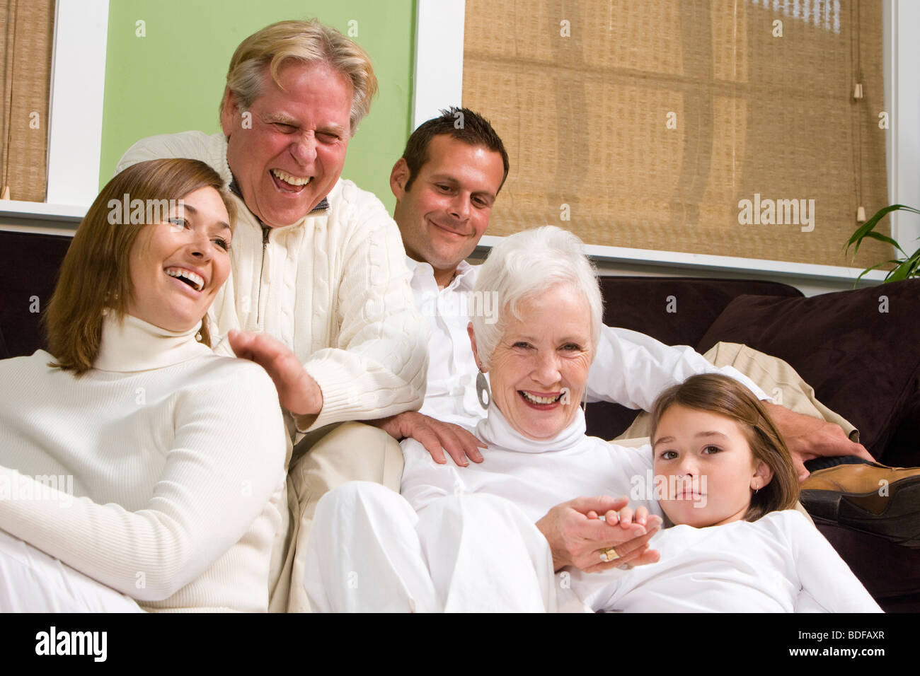Happy multi-generational family posing in living room - Stock Image