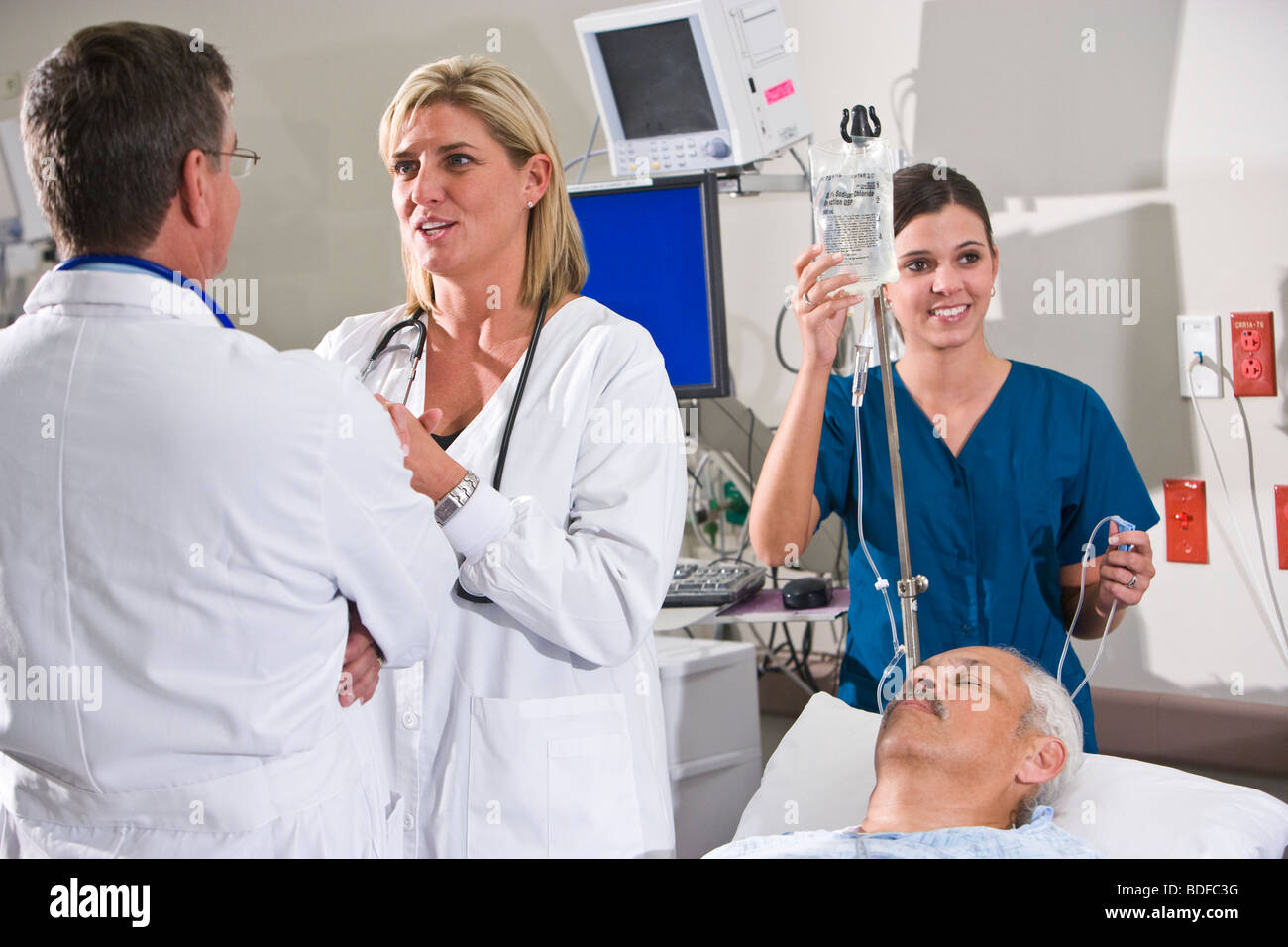 doctors and nurse in hospital room with patient stock photo