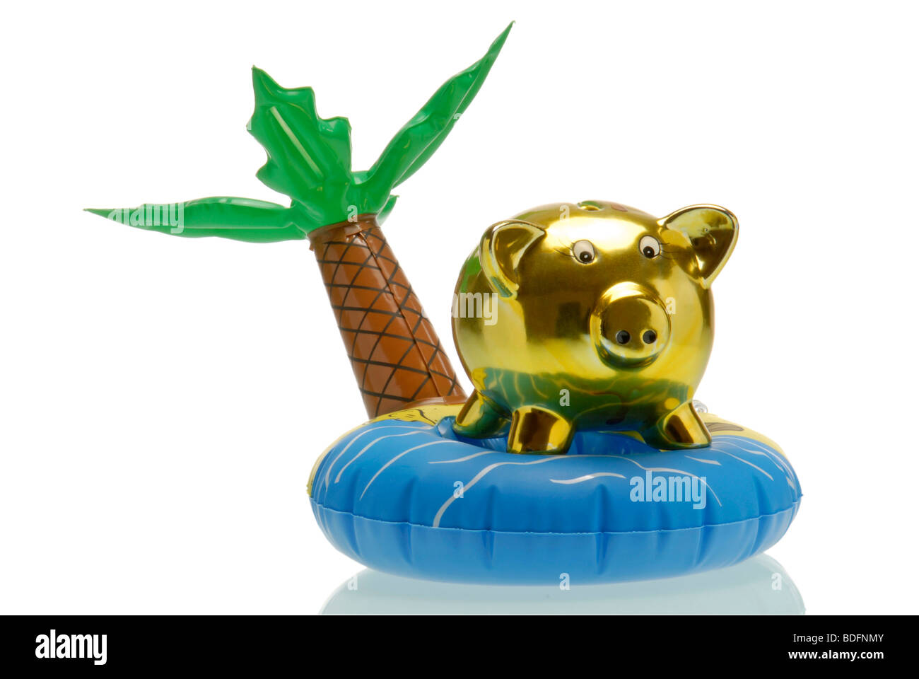 Piggybank on plastic island, symbolic picture for tax haven - Stock Image