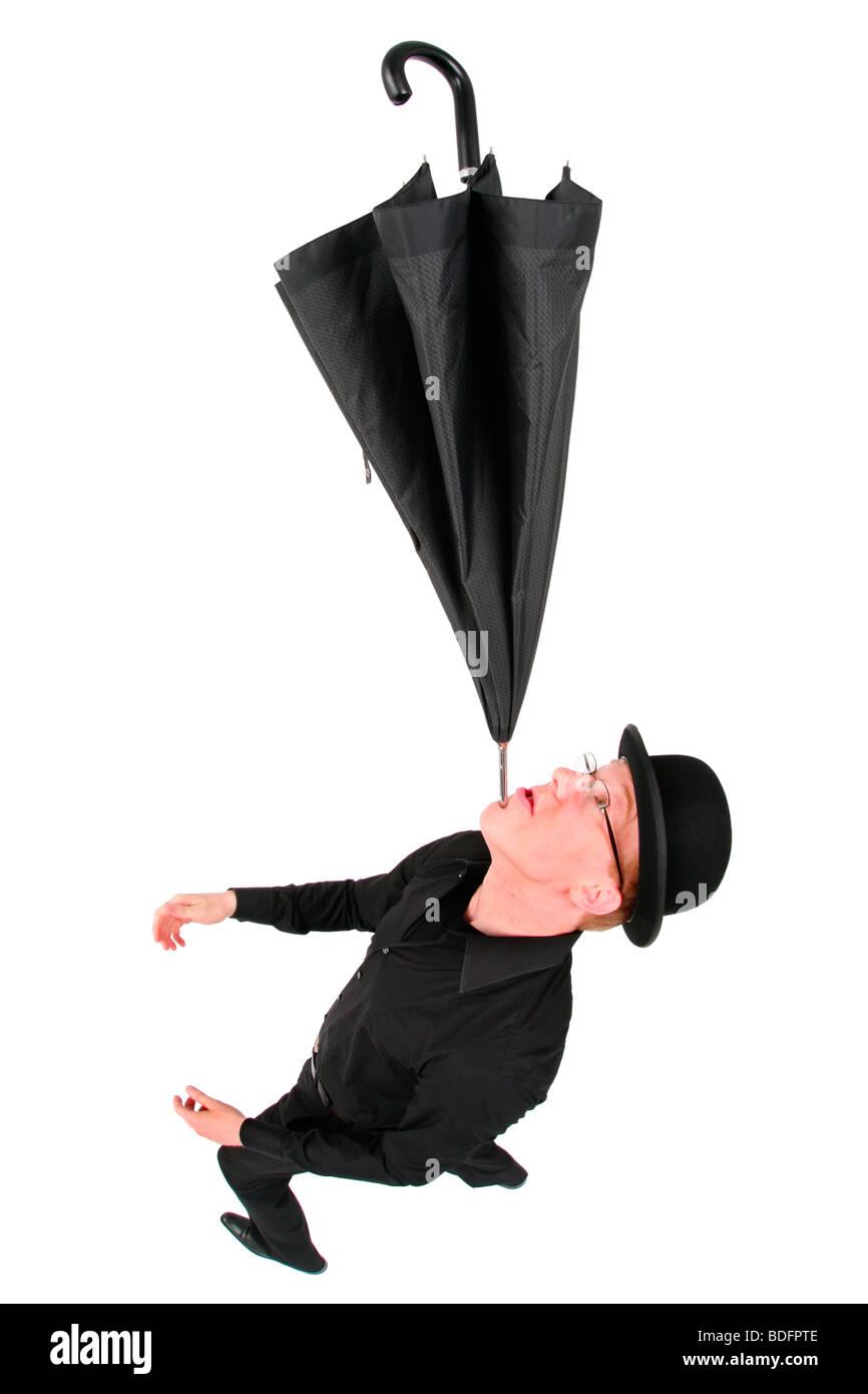 young man with bowler hat balancing an umbrella on his chin - Stock Image