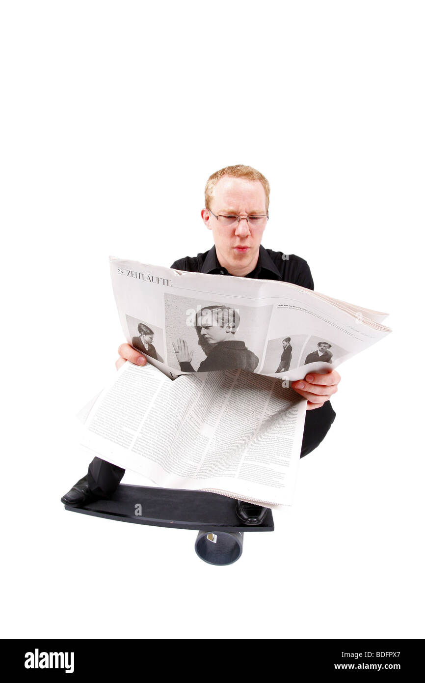 young man on board reading newspaper and balancing on roll Stock Photo