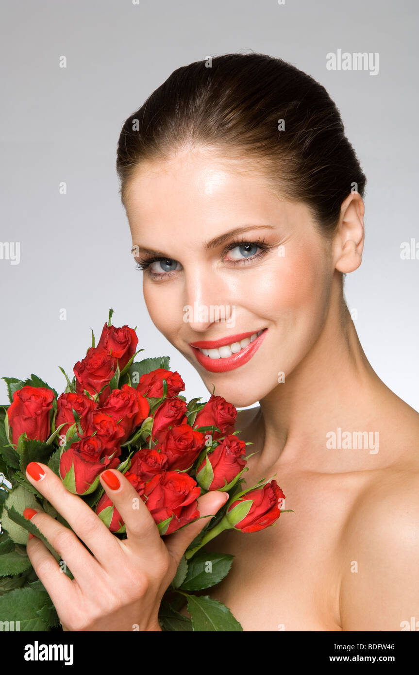 Female beauty model smelling roses - Stock Image