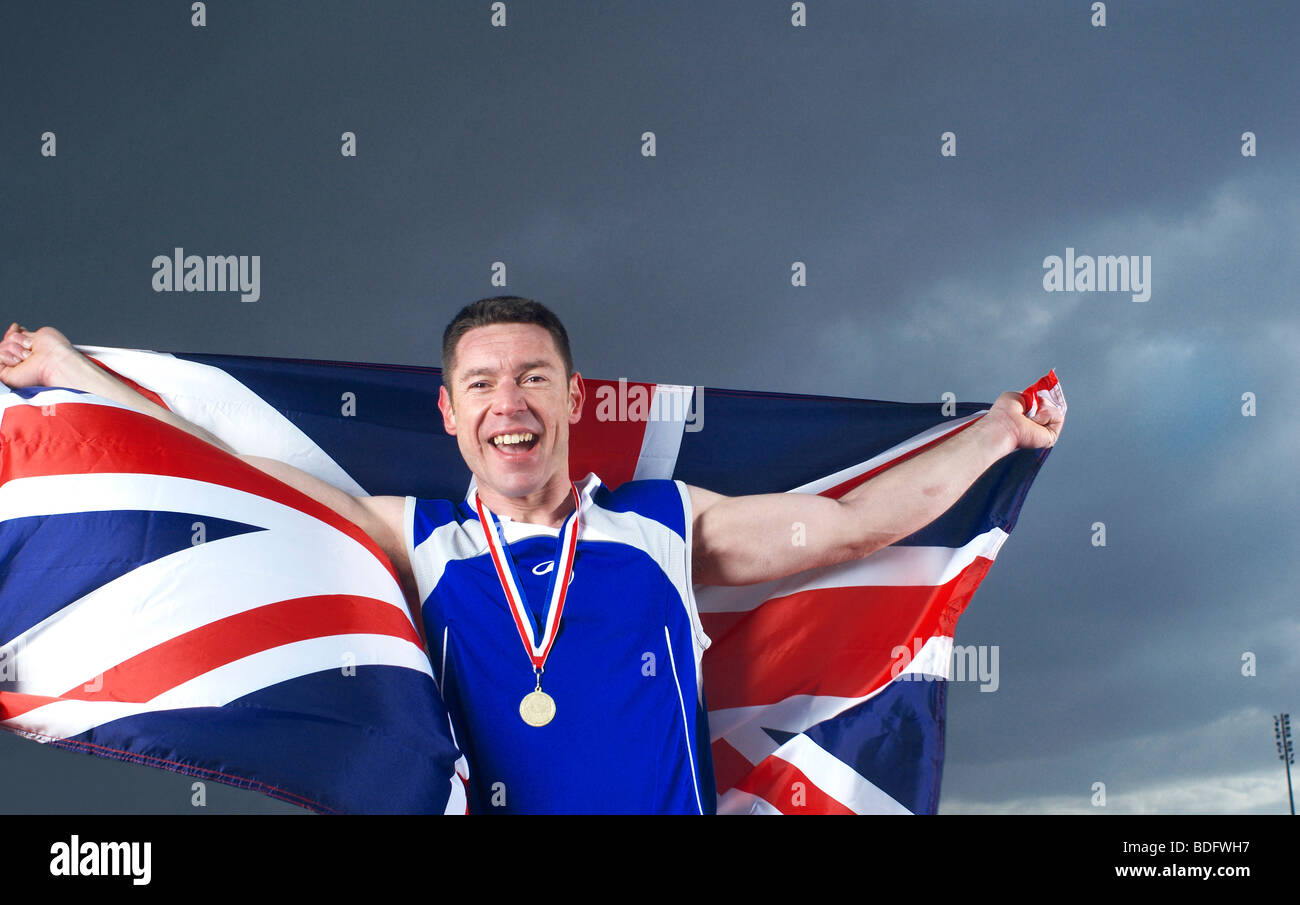athlete cheering with U.K. flag and medal - Stock Image
