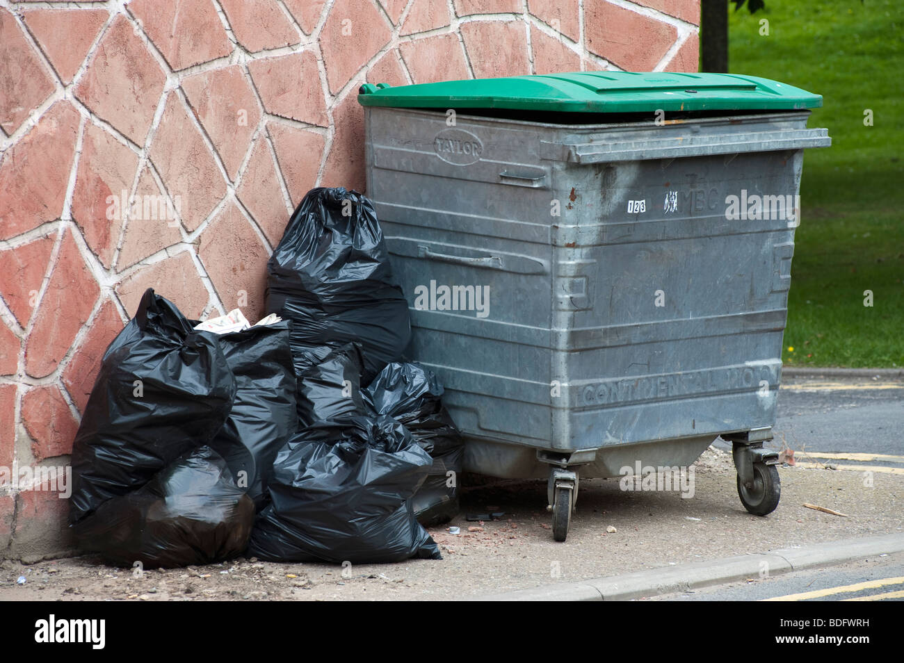 Wheeled waste bin and black rubbish bags awaiting collection - Stock Image