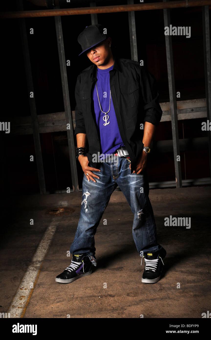 African American hip hop dancer standing over industrial background - Stock Image