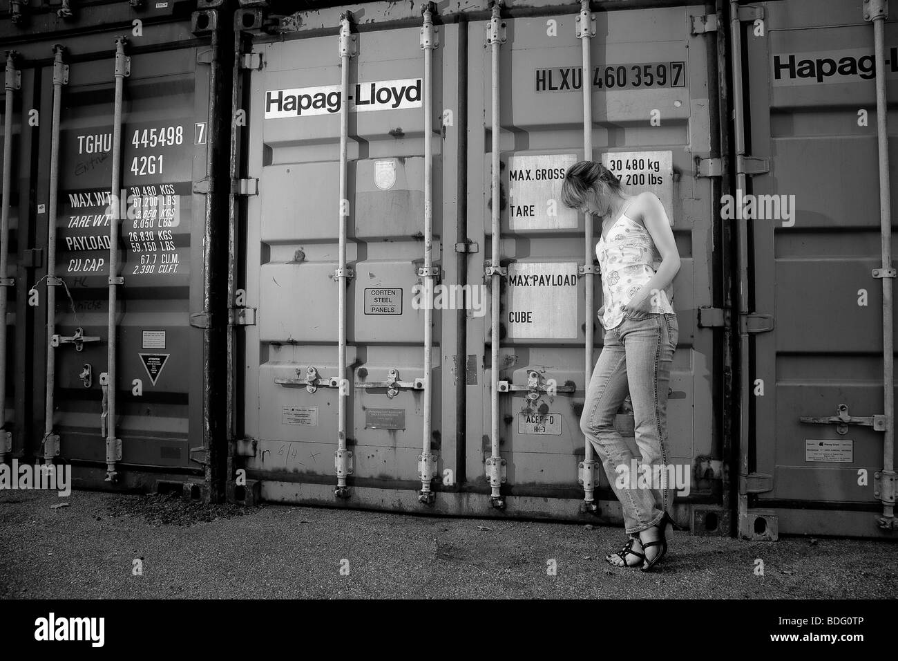 Young woman standing in front of a container - Stock Image
