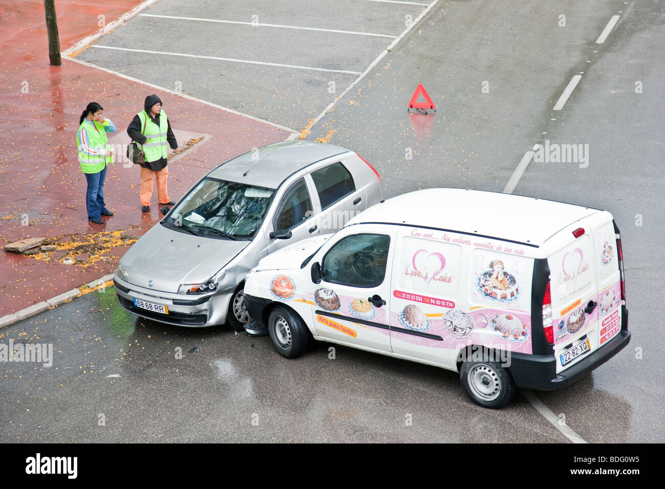 Two women (drivers) wait for the police after a car accident on a rainy day due to excessive speed. - Stock Image