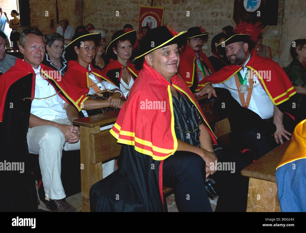 Members of Madiran's local confrérie, the Viguerie Royale, and associated brotherhoods in church during - Stock Image