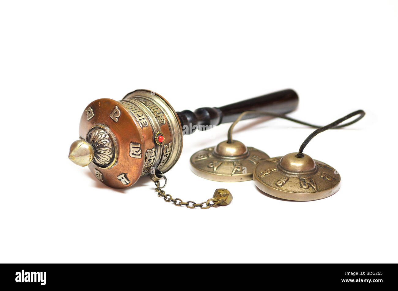 Tibetan brass cymbals and a prayer wheel - Stock Image