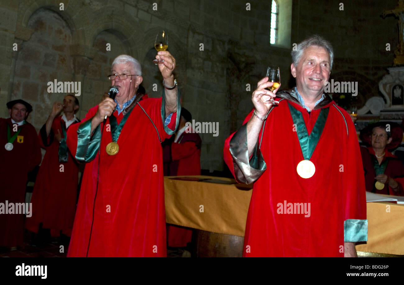 Robed members of Madiran's local brotherhood, Viguerie Royale, call for a toast during their annual wine festival - Stock Image