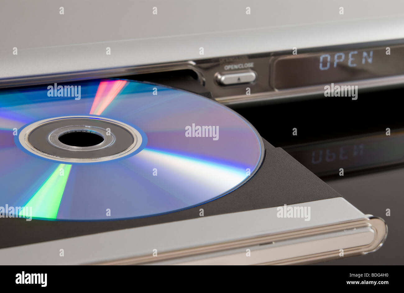 DVD disc inserted in DVD player disc tray isolated on black background - Stock Image
