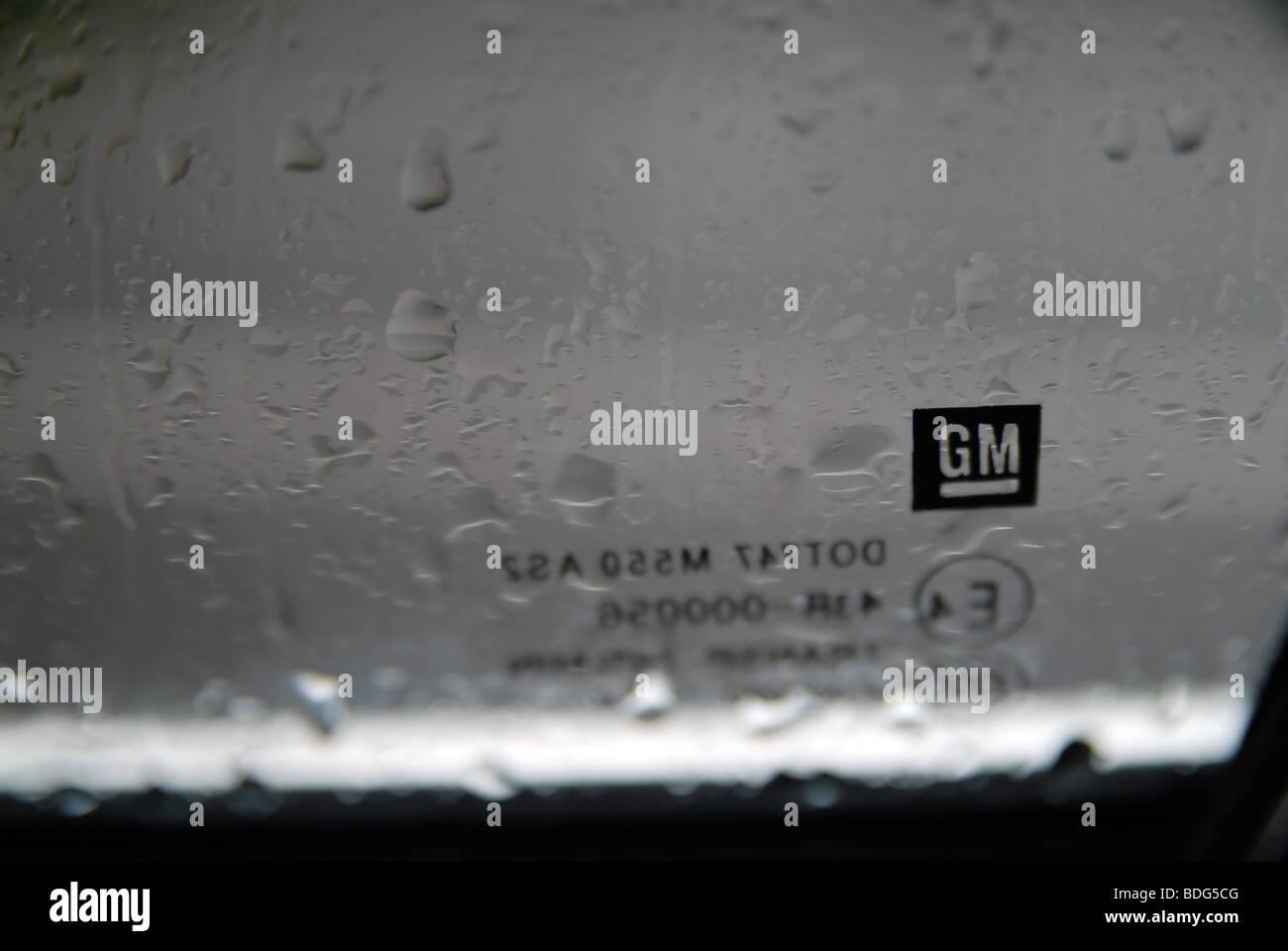 GM - General Motors logo on a car windscreen in the rain - Stock Image