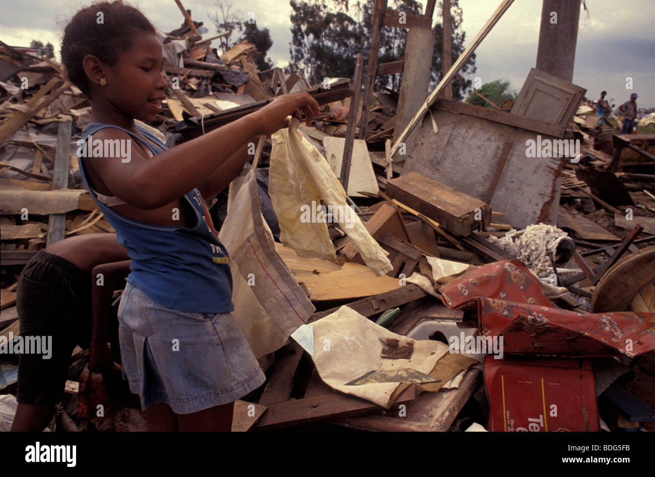 Homeless families being evicted from invaded area. Tractor destroyed their houses. Children look for missing things. - Stock Image