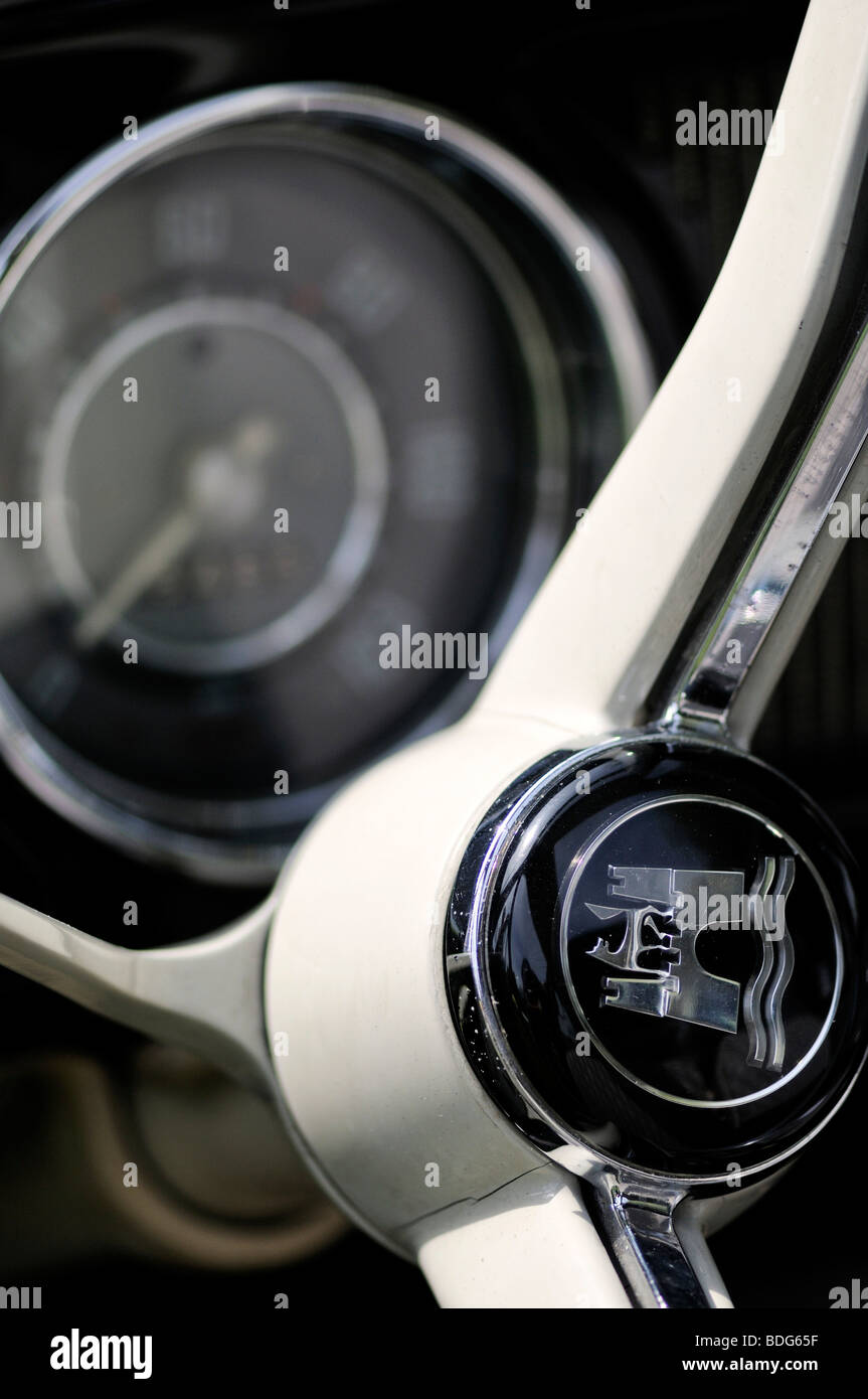Wolfsburg's coat of arms on the steering wheel of an old VW Beetle, in the back the speedometer, Germany - Stock Image