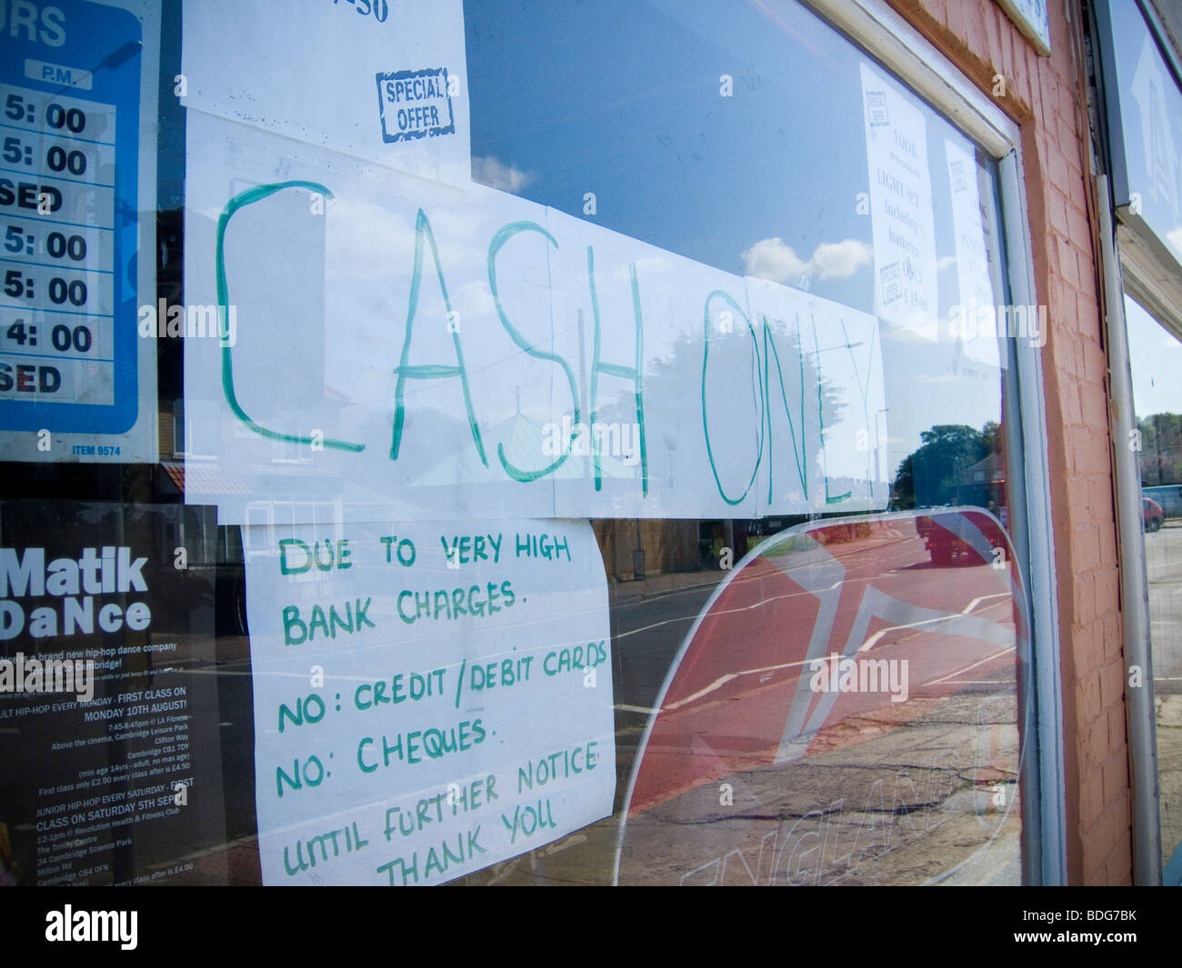 A CASH ONLY sign in a shop window, with a complaint/comment about high bank charges. - Stock Image