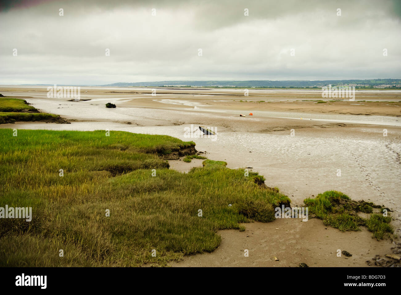 Low tide exposing the mudflats of the Llanrhidian sands on the Loughor estuary, south  west wales UK, overcast grey - Stock Image