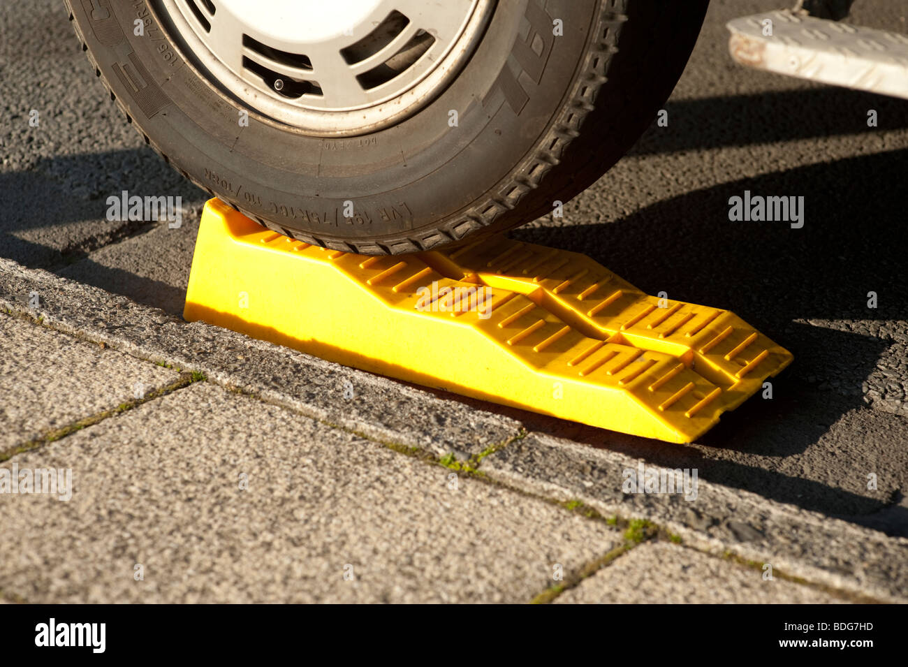 yellow plastic step wedge chocks placed under the wheel of a camper van to level the vehicle when parked on the - Stock Image