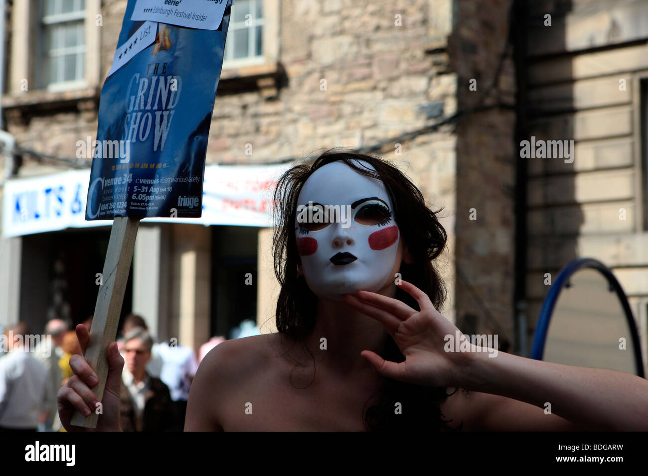 Girl with a white mask on promotes The Grind Show at the Edinburgh Fringe Festival 2009 - Stock Image