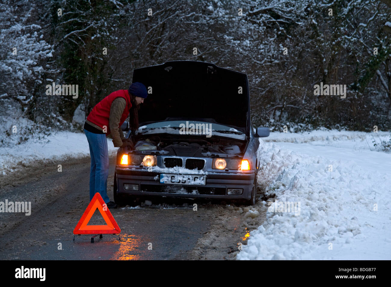 Women on her own broken down in the snow, stranded trying to get it fixed. - Stock Image