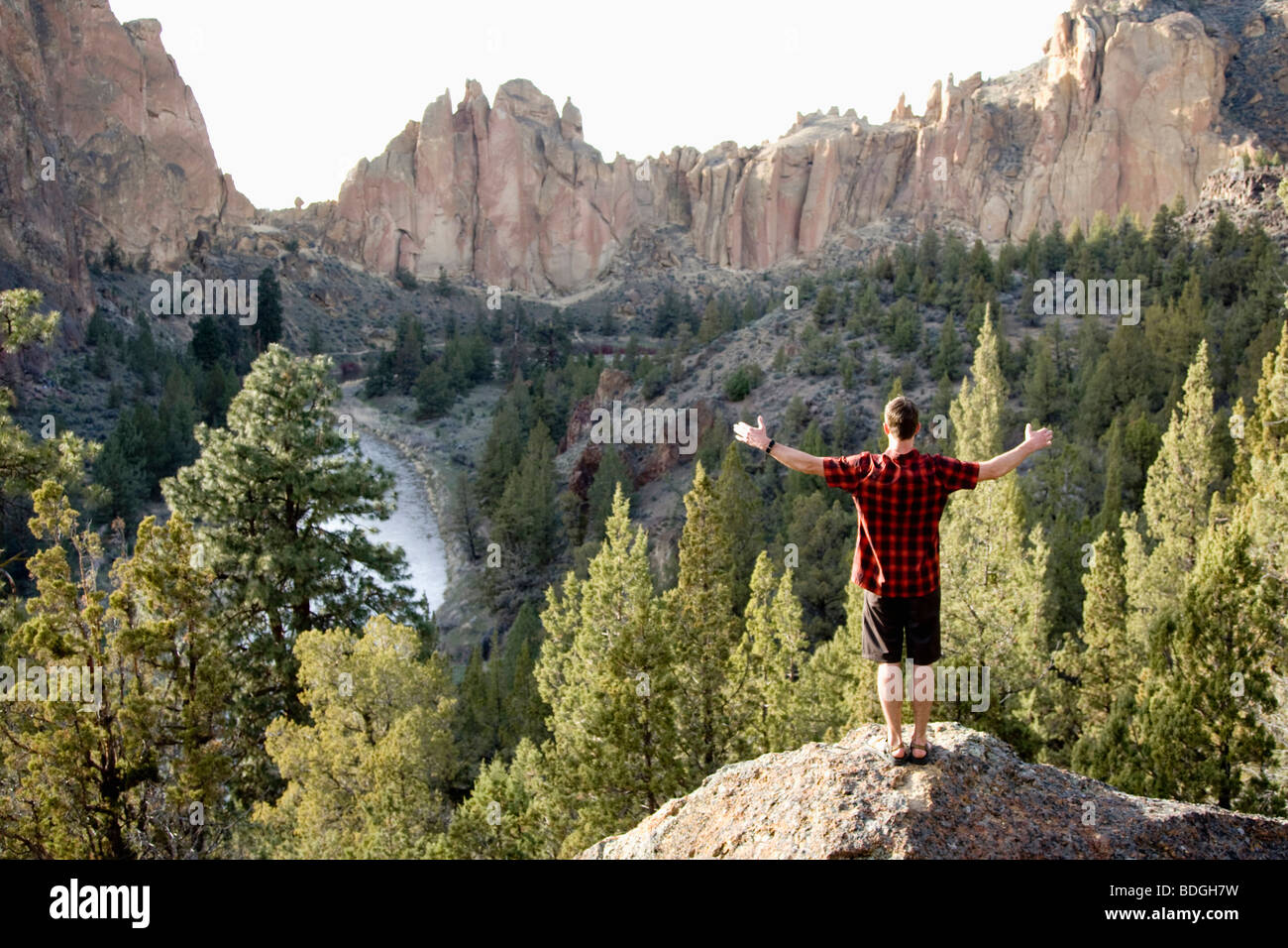 A man in a plaid shirt stands with his arms wide open overlooking the Crooked River Valley below. Stock Photo