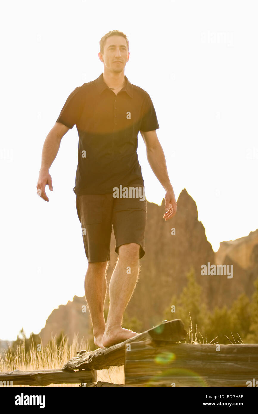A man does his best to balance while walking on  thin log. (solar flare) - Stock Image