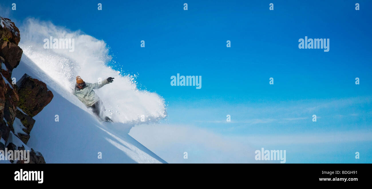 Snowboarder carving through powder snow in front of a blue sky. - Stock Image