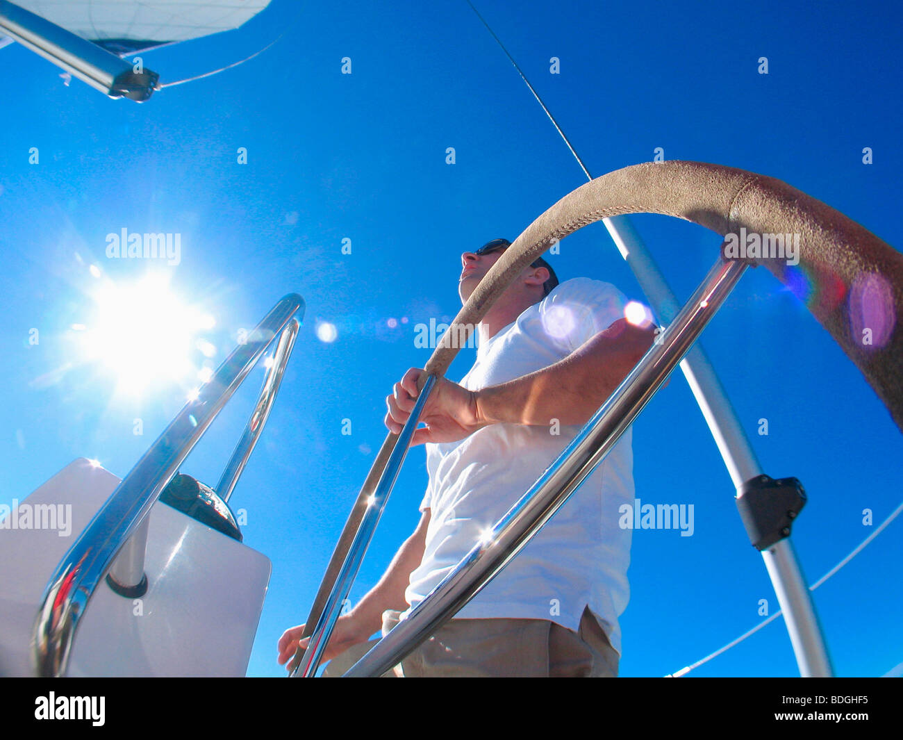A skipper steering on board a yacht under blue skies while cruising in Pittwater on the North Shore from Sydney, - Stock Image